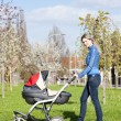 Woman with a pram on spring walk — Stock Photo #9970589