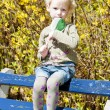 Little girl with a lollipop sitting on bench in spring — Stock Photo #9970596