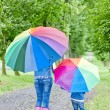 Mother and her daughter with umbrellas in spring alley — Stock Photo #9970719