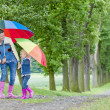 Mother and her daughter with umbrellas in spring alley — Stock Photo #9970722