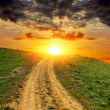 Stock Photo: Dirty road to sunset