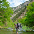 Stock Photo: Hiker crosses river