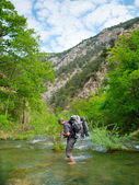 Hiker crosses a river — Stock Photo