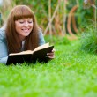 Stock Photo: Young woman reading a book lying on the grass