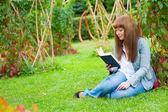 Młoda kobieta, czytając książkę leżąc na trawie — Zdjęcie stockowe