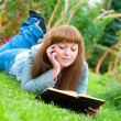 Young woman reading a book lying on the grass — Stock Photo