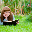 Young woman reading a book lying on the grass — Stock Photo #9332151