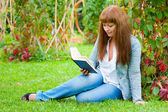 Young woman reading a book lying on the grass — Стоковое фото