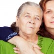 Family studio portrait - happy daughter and her old mother — Stock Photo