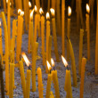 Wax candles burning in church for Easter - Stock Photo
