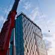 Tall crane and office building in construction — Stock Photo