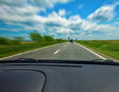 Fast car on road viewed from the interior — Stock Photo