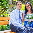 Happy married couple sitting on bench - Stock Photo