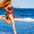 Happy sexy woman jumping on the beach — Stock Photo
