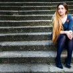 Grunge portrait of pensive beautiful woman on steps — Stock Photo