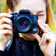 Female photographer with photo camera in hands — Stock Photo