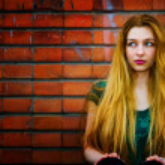 Blond woman and brick wall — Stock Photo #9921726