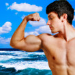 Muscular man showing his biceps on the beach — Stock Photo #9922255