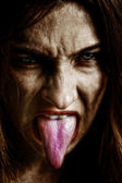 Evil scary sinister woman with tongue out — Stock Photo