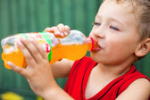 Boy drinking unhealthy bottled soda — Stock Photo