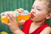 Boy drinking unhealthy bottled soda — Stock Photo