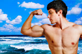 Muscular man showing his biceps on the beach — Stock Photo
