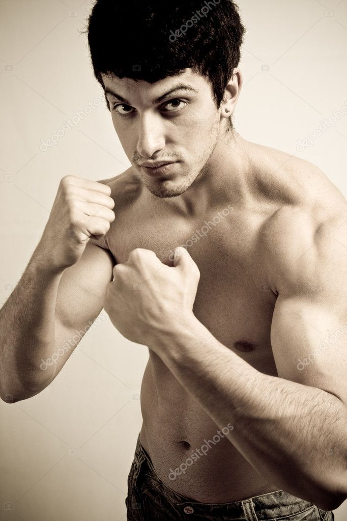 Portrait of muscular male fighter with fists ready to punch — Stock Photo #9922259