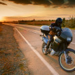 Stock Photo: Biker and motorcycle on road at sunset