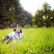 Kiss of romantic lovers in the green grass — Stock Photo #9933361