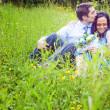 Couple having a candid romantic kiss in the grass — Stock Photo #9933363