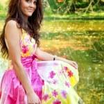 Woman with beautiful colorful dress near lake — Stock Photo