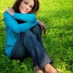 Serene beautiful woman resting on green grass — Stock Photo