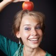 Woman with healthy teeth and apple on head — Stock Photo