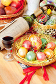 Easter painted eggs with wine bottle and glass — Stock Photo