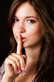 Gossip - woman with finger over lips — Stock Photo