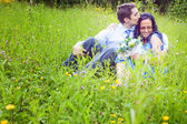 Couple having a candid romantic kiss in the grass — Stock Photo