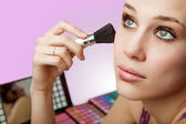 Makeup and cosmetics - woman using blush brush — Stok fotoğraf