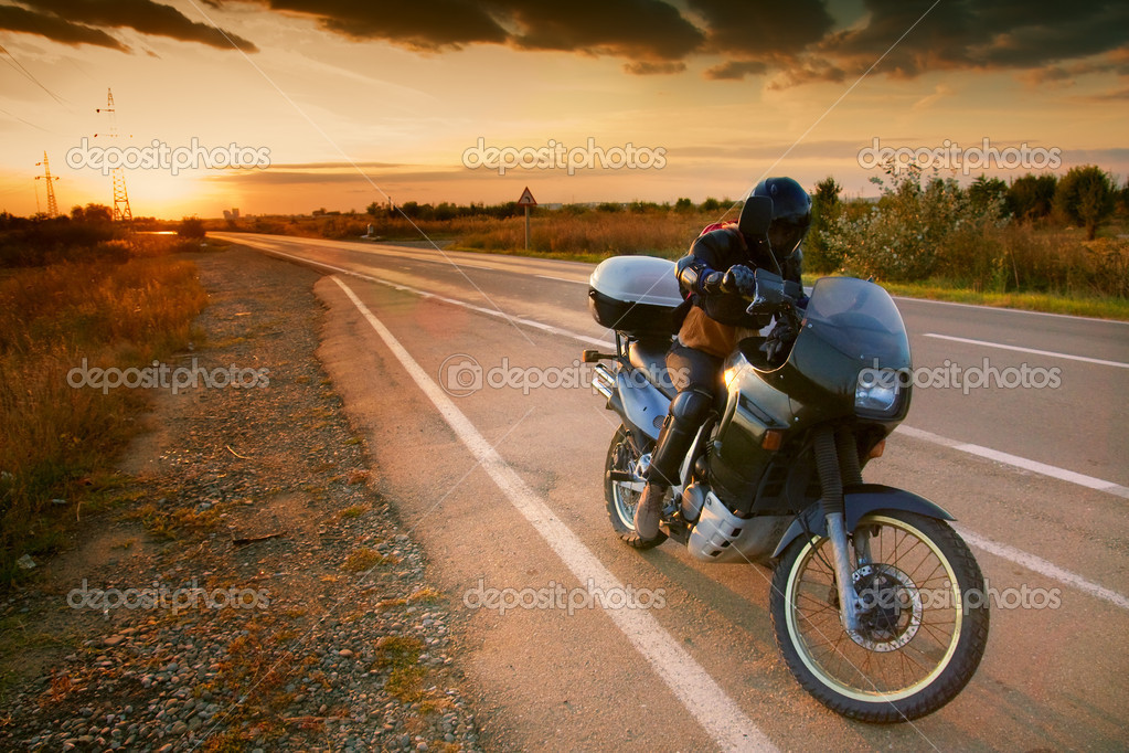 Biker and motorcycle on the road at sunset — Stock Photo #9932603