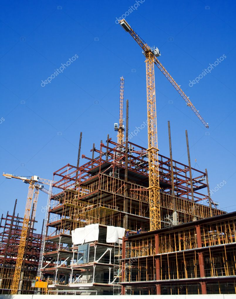 Construction site with big yellow cranes and blue sky — Stock Photo #9932742