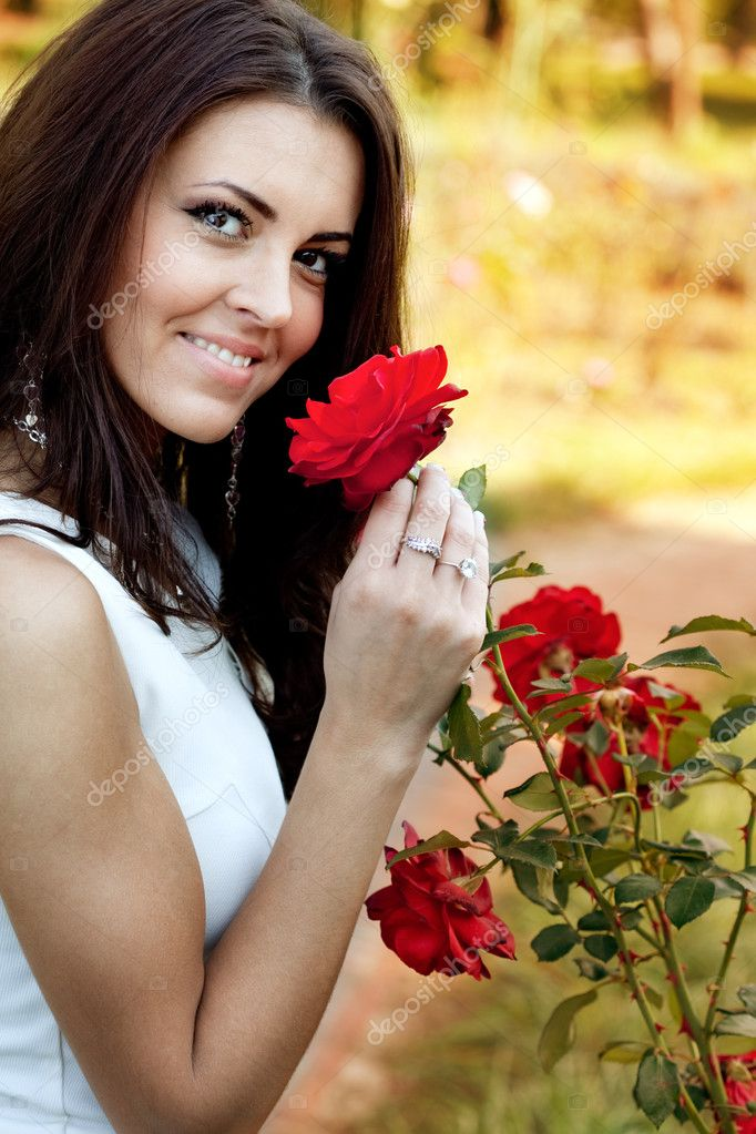 Happy young woman in flower garden smelling red roses — Stock Photo #9933492