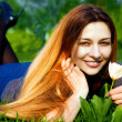 Happy young woman and flower in fresh grass — Stock Photo