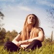 Calm woman relaxing in sunny grass field — Stock Photo