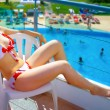 Woman in bikini relaxing at summer holiday resort — Stock Photo