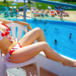 Woman in bikini relaxing at summer holiday resort — Stock Photo #9980741