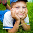Cute happy kid laying on grass outdoor — Stock Photo #9980742
