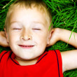 Happy dreaming child on fresh grass — Stock Photo