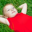 Pensive child day dreaming in fresh grass - Stock Photo