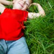 Happy joyful boy relaxing on fresh grass — Stock Photo