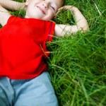 mutlu neşeli çocuk Taze çimenlerin üzerinde rahatlatıcı — Stok fotoğraf #9980755