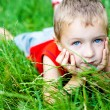 Cute boy relaxing on green fresh grass — Stock Photo